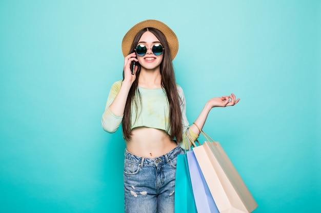 Donna castana casuale allegra che parla sullo smartphone e che tiene i sacchetti della spesa isolati sopra verde
