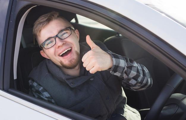 큰 흰색 차에 앉아 엄지 손가락을 행복하게 보여주는 쾌활한 캐주얼 남자
