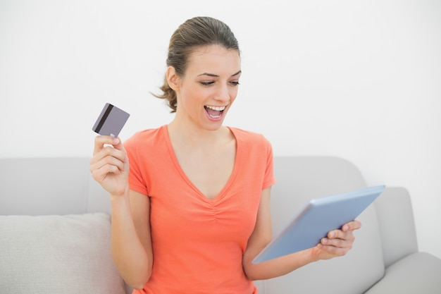 Cheerful casual woman home shopping with her tablet sitting on couch
