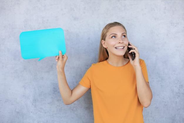 회색 배경 위에 격리된 쾌활한 캐주얼 젊은 여성이 휴대전화로 통화하고 빈 말풍선을 보여줍니다. 프리미엄 사진