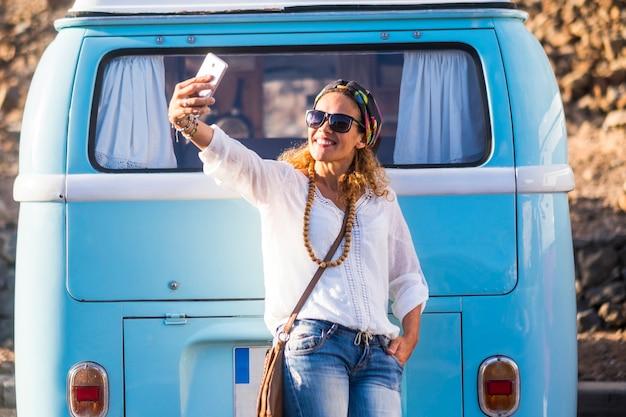 陽気な白人40歳の女性が笑顔で携帯電話で自分撮り写真を撮る