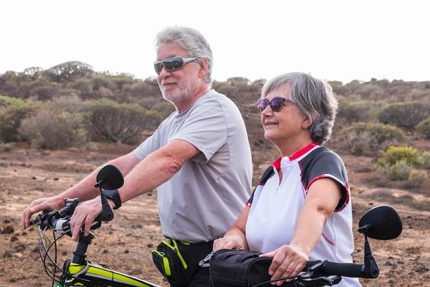 건강한 스포츠 야외 여가 활동을 함께하는 산악 자전거와 쾌활한 백인 성인 수석 부부-노인은 자연 속에서 노인을 타고 즐기는 라이프 스타일을 즐깁니다. 프리미엄 사진