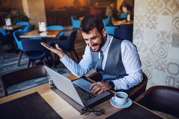 Cheerful caucasian bearded handsome businessman sitting in cafe and using laptop. on table are laptop, coffee, eyeglasses and water.