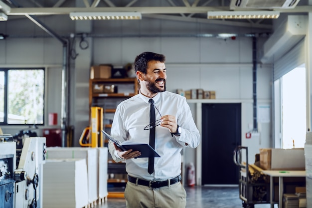 Cheerful caucasian bearded supervisor in shirt and tie holding notebook and eyeglasses while walking around printing shop.