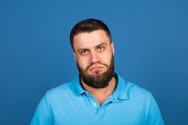 Cheerful. caucasian beautiful man's portrait isolated on blue  wall with copyspace. male model with beard.