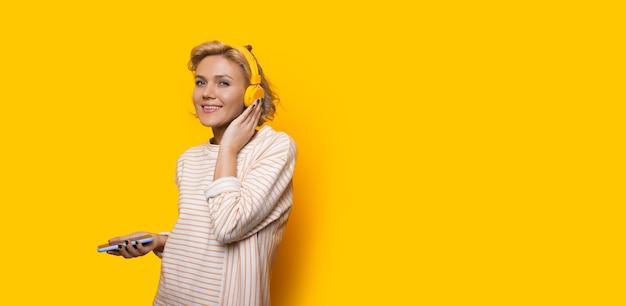 Веселая кавказская блондинка слушает музыку с телефона, позируя возле желтого свободного пространства