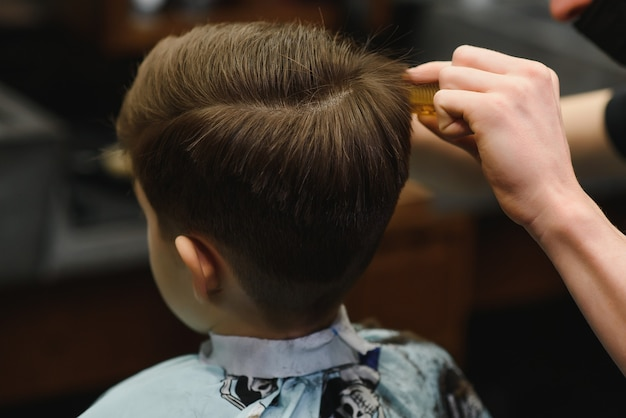 Веселый кавказский мальчик, получающий прическу в парикмахерской.