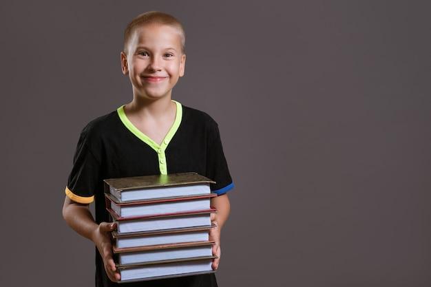 黒のtシャツを着た陽気な白人の少年は、灰色の背景に本のスタックを保持しています。教育の概念