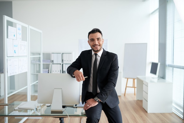 Cheerful caucasian businessman sitting on desk in office, leaning on screen and smiling