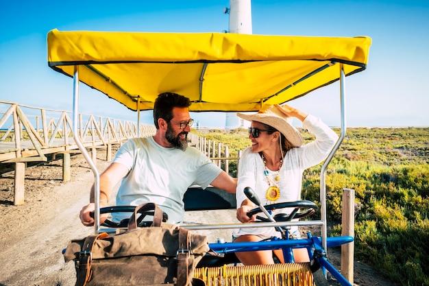 カートに乗って休暇を楽しんでいる陽気な白人カップル。オープンカートを運転してフィールドを旅する幸せなカップル。一緒に余暇を過ごすカップル