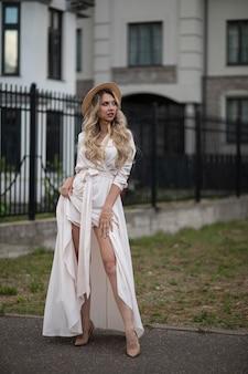 長いブロンドの髪、青い目、帽子をかぶった長い白いドレスを着た完璧な笑顔の陽気な白人女性が家の近くを歩いています