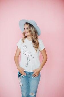白いt-shite、ブルージーンズ、大きな青い帽子の笑顔で長いウェーブのかかった金髪の陽気な白人女性
