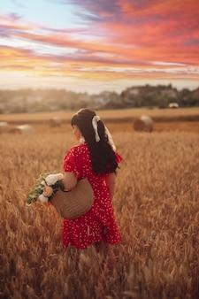 彼女の手にバッグと花と赤いドレスの波状の長い黒髪の陽気な白人女性