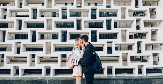明るい色の服を着た陽気な白人の女の子は、うまく設計された建物の前で彼女の黒い服を着た恋人にキスします