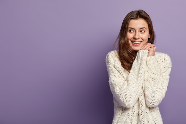 Cheerful caucasian girl keeps hands together near face, looks positively aside, has no make up, healthy skin, wears white sweater, stands over purple wall with blank space for your promotion