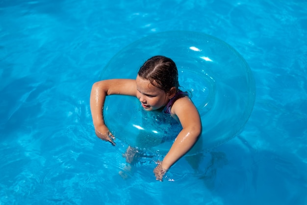Cheerful caucasian girl swims in the clear water of the sea hanging her hands on a blue inflatable c...