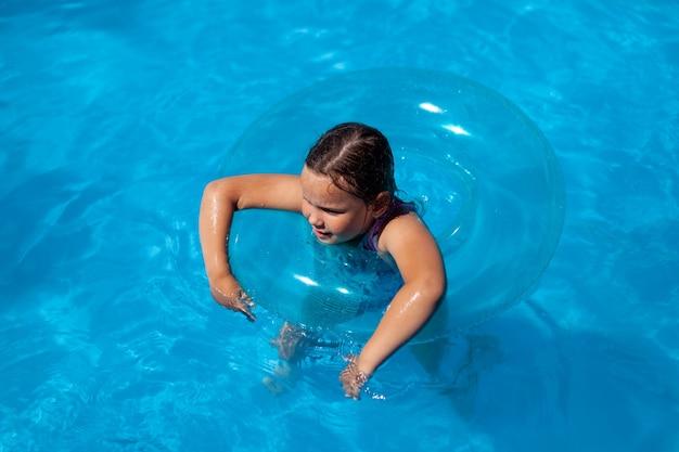 陽気な白人の女の子は、青い膨脹可能なcに手をぶら下げて海の澄んだ水で泳ぎます...