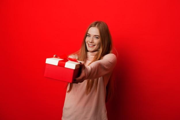Веселая кавказская девушка с рыжими волосами и веснушками держит подарок, позируя на красном фоне