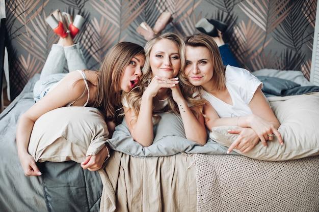 陽気な白人の女の子はベッドに横たわって、大きな明るい寝室で彼らの人生と笑顔を楽しんでいます