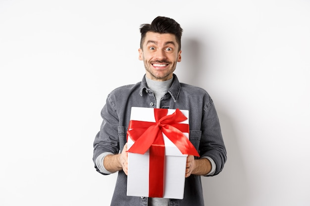 Cheerful caucasian guy holding surprise gift, receive present on holiday and smiling thankful, looking grateful at camera, celebrating valentines day, white.