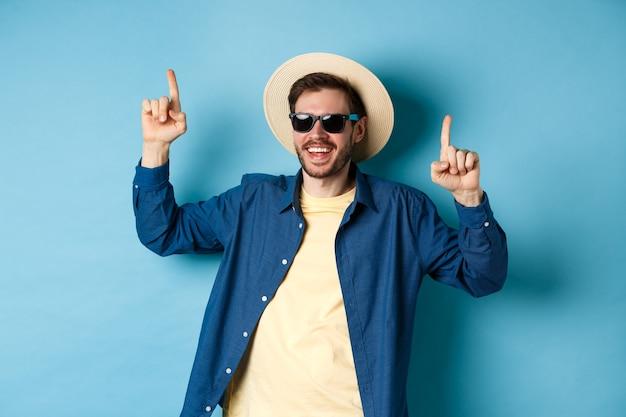 麦わら帽子とサングラス、ダンス、休暇で楽しんで、青い背景の上に立っている陽気な白人の男。夏の観光の概念。