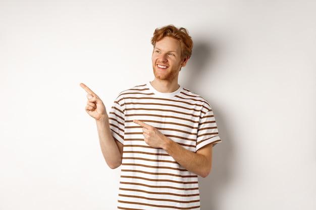 赤い髪とあごひげを持つ陽気な白人の男は、白い背景の上に立って、ロゴのバナーを左に見て指しています。