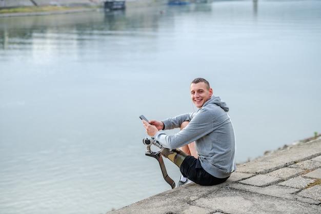 쾌활한 백인 장애인 스포츠맨 스포츠웨어와 인공 다리가 강 옆에 앉아 카메라를 보면서 스마트 폰을 고소합니다.