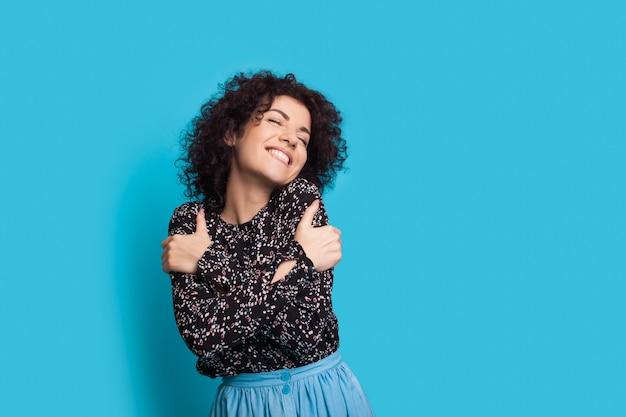 笑顔で青い背景に身を包む巻き毛の陽気な白人女性
