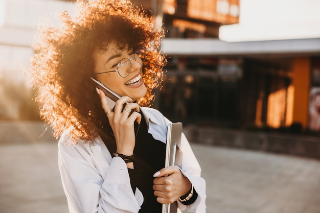 Cheerful caucasian lady with curly hair and eyeglasses is holding laptop while walking and talking on phone