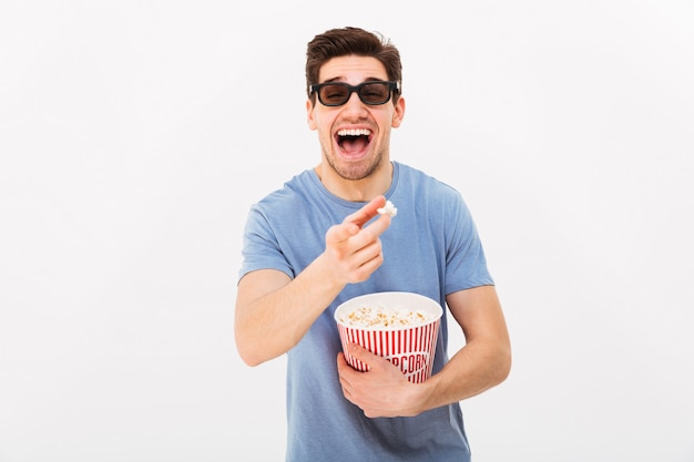 Cheerful caucasian man in casual t-shirt and 3d glasses holding bucket with popcorn while watching movie in cinema, isolated over white wall