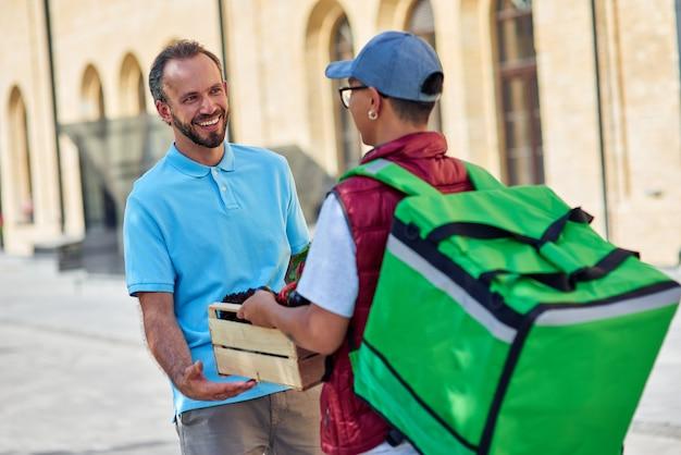 쾌활한 백인 남성 고객이 남성 택배사로부터 신선한 식료품이 든 나무 상자를 받고 있습니다.