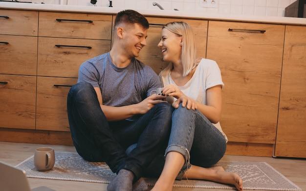 Веселый кавказский мужчина сидит на полу на кухне рядом со своей девушкой, попивая кофе