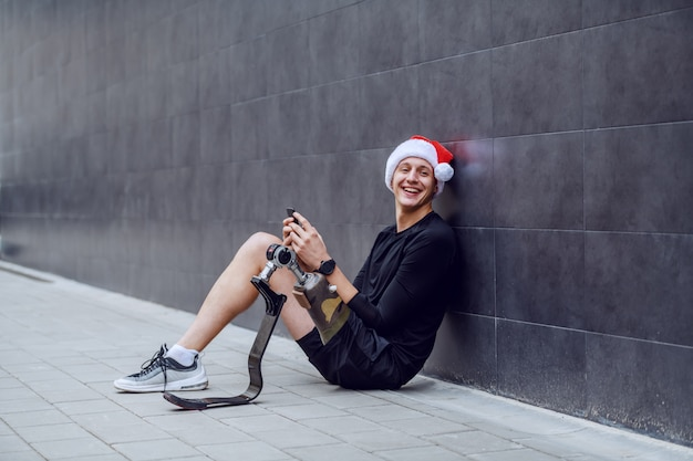 義足と地面に座って頭にサンタの帽子をかぶった壁に寄りかかって、クリスマスの願いをスマートフォンで送る陽気な白人スポーツマン。