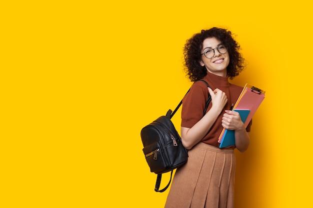 バッグといくつかの本を持っている陽気な白人学生は、空きスペースのある黄色の背景で楽しくポーズをとっています