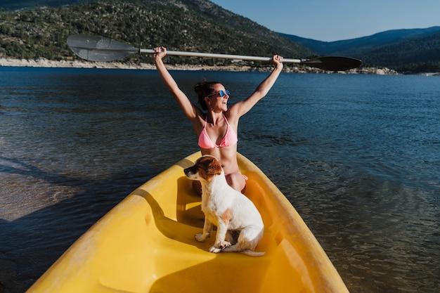 Веселая кавказская женщина и собака джек рассел, сидя на желтом каноэ в озере в солнечный день. летнее время. женщина, держащая весло. домашние животные, приключения и природа