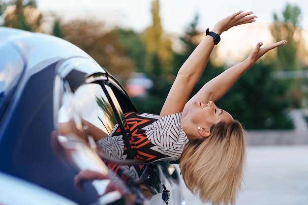 Cheerful caucasian woman drives through the picturesque sunny city and waves her arms while stretching out of the car window on a beautiful day