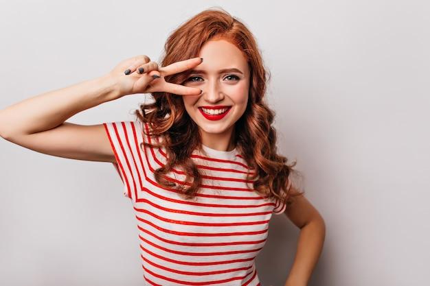 ピースサインでポーズをとって赤いtシャツを着た陽気な白人女性。白い壁で笑っている生姜の感情的な女の子の屋内写真。