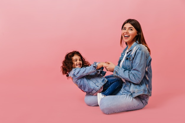 Cheerful caucasian woman playing with daughter. studio shot of preteen curly child sitting with mom on pink background.