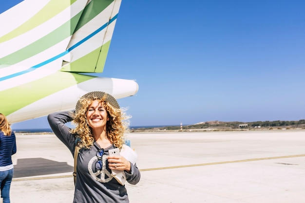 携帯電話と旅行休暇旅行の準備ができて飛行機の前に巻き毛と帽子を持つ陽気な白人女性。飛行機の前の飛行場で興奮した女性の乗客