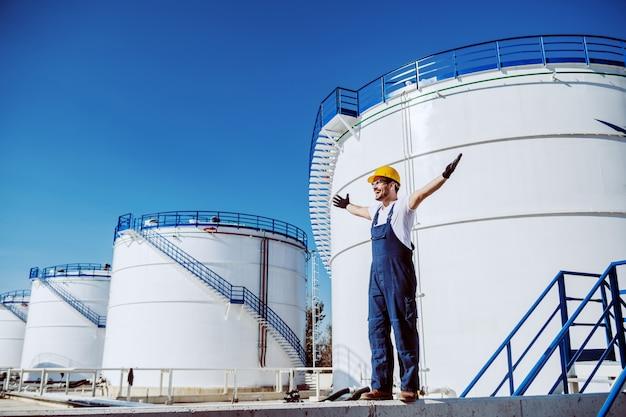 Жизнерадостный кавказский работник в целом и с шлемом на голове стоя outdoors с раскрытыми рукоятками. на заднем плане - нефтяные резервуары.