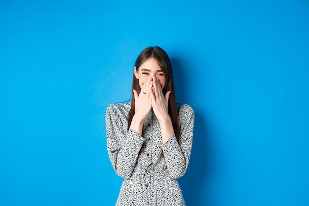 青の上に立って、笑って楽しんで、手で口を覆い、面白いものを笑いながらドレスを着た陽気なコーカシーナの女の子。