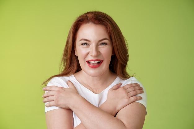 쾌활한 카리스마 행복 잘 생긴 빨간 머리 여자 빨간 립스틱 크로스 손 가슴 웃고 동기 부여 흥분 재미 장난 스릴 기분 웃 고 열정적 인 서 녹색 벽