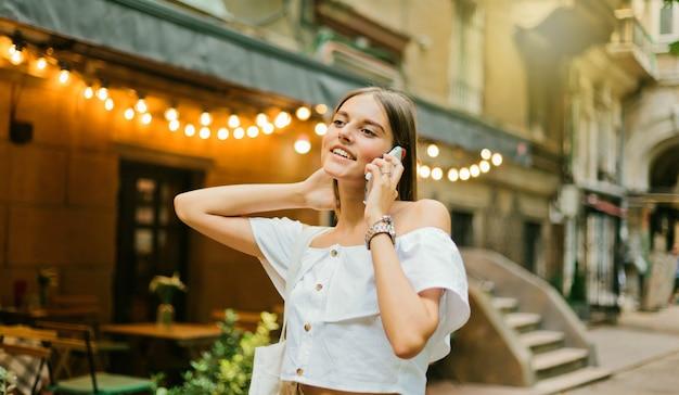 夕方に歩きながら電話で話している陽気なカリスマ的な女性