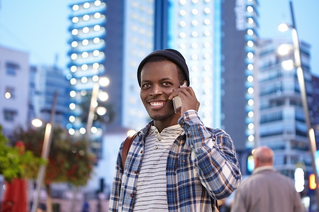 Cheerful charismatic young afro american student in stylish wear smiling happily while having phone conversation with his old friend