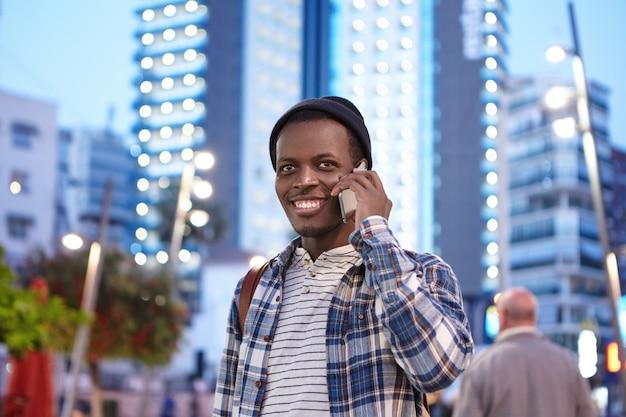 Giovane studente afroamericano carismatico allegro nell'abbigliamento alla moda che sorride felicemente mentre avendo conversazione telefonica con il suo vecchio amico
