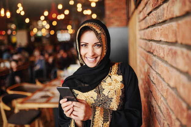 Cheerful charming muslim woman in abaya using smart phone for reading or writing message while sitting in cafeteria.
