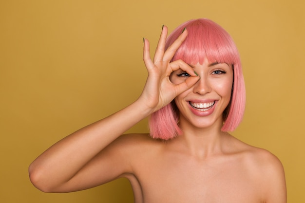Cheerful charming young blue-eyed pink haired female with bob hairstyle being in high spirit and smiling happily while standing over mustard wall with raised ok sign