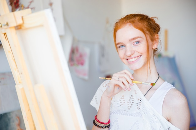 Cheerful charming young female artist painting  with paintbrush on canvas in art studio