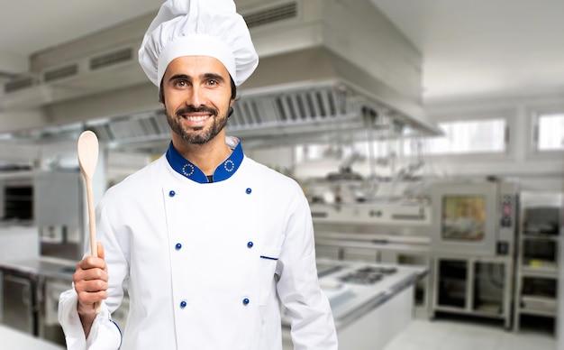 彼の台所で木のスプーンを持っている陽気なシェフ