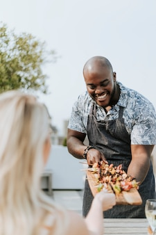 Cheerful chef serving grilled vegan barbeque skewers